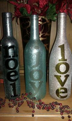 Wine bottles + stick on letters + spray paint = holiday vases.. I love that these aren't traditional christmas colors. Gives a more winterland feeling.