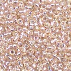 Miyuki 11/0 (2mm) Silver-Lined Light Blush AB round rocaille glass seed beads, colour number 1023. Transparent pale pink outside, shiny inside, with an iris rainbow finish. UK seller.
