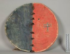 Ceremonial Shield, Hidatsa Arikara Mandan. Dakota Territory / North Dakota. Collector: Brig. Gen. William B. Hazen William Courtenay, 1872. Painted buckskin stretched over a wooden hoop. Tribal identification changed from Sioux to Hidatsa, Arikara, or Mandan by Candace Greene May 2017 based on a full review of the collecting history and consideration of general stylistic traits. NMNH.