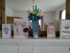 Homemade crepe paper flowers in a homemade vase to complement a teal and cream lounge and a homemade card with  vintage Parisian imagery