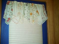 I made this from vintage handkerchiefs.  I simply tacked with needle and thread each handkerchief over a basic white curtain rod.  Turned out lovely!!!