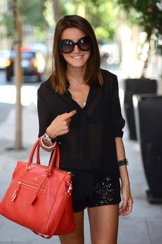 the red handbag creates a nice pop of color to this otherwise all black outfit.