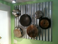 Corrugated metal wall pot rack. Key West home. Stainless steel peg board hooks.