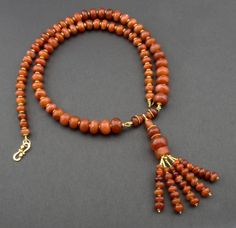 """A necklace made of a collection of matched ancient carnelian beads (as documented and discussed by M-F. Delarozière in """"Perles d'Afrique""""), with a tassel of the same, and further enriched with gold beads from India. When hanging from a nail on the wall, the necklace is 39 cm (15,35"""") long, including the tassel. Carnelian agate, 18K gold."""