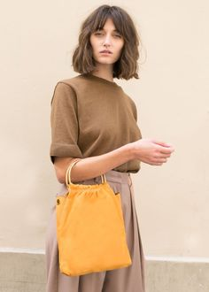 "#newarrivals #mustard #ring #suede #bag #accessories #thefrankieshop #frankienyc #frankiegirl Textured Leather Flat Bag w/Brass Metal Ring Handles & Detachable Self Leather Shoulder Strap 10""L x 15""H x 1""D Imported"