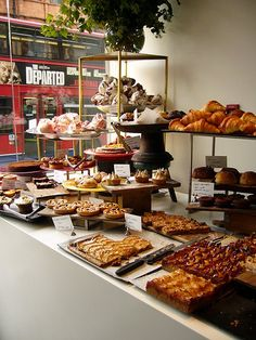 Muffins, cake etc. arranged like this on the front counter but partitioned from customers with glass