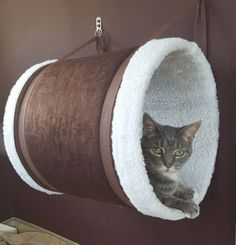 """Check out these gorgeous cat tunnels, all handmade with beautiful designer fabrics and plush faux fur liners. The exquisite quality makes them look more like fine furniture than a cat hideaway! Each tunnel measures 12"""" in diameter and 16"""" long. They hang from the wall with two sturdy straps and metal wall hooks. According to the… #cathousefabric #cathousehandmade"""