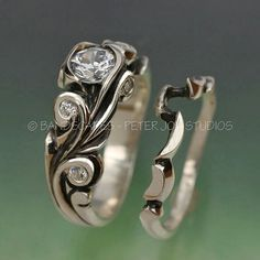 This ring is deeply carved with scrolls that curl into settings for the small stones, as well as the large center. The side stones are each 2mm and