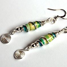 More paper bead earrings + my very first necklace :D - JEWELRY AND TRINKETS - I feel like I'm mass-producing jewellery now, but it's so much fun I came across this photo of a beach dress with a really colourful pattern Make Paper Beads, Paper Bead Jewelry, Paper Earrings, Fabric Jewelry, Bead Earrings, How To Make Beads, Jewelry Crafts, Beaded Jewelry, Wire Jewelry