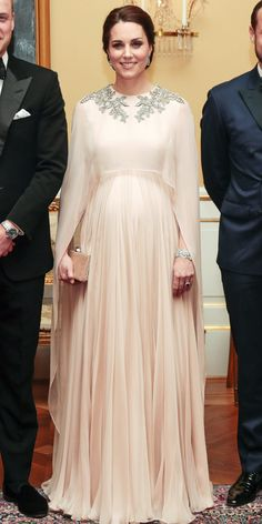 Look of the Day: For a formal dinner, Kate Middleton made an unforgettable entrance wearing a regal Alexander McQueen gown with a see-through cape. But we really can't stop staring at all of those sparkling jewels. Kate Middleton Outfits, Vestidos Kate Middleton, Looks Kate Middleton, Kate Middleton Pregnant, Maternity Gowns, Maternity Fashion, Vestidos Para Baby Shower, Hijab Fashion, Fashion Dresses