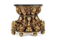 Base/consola, em madeira profusamente entalhada, decorada com cabeças de anjo, folhas de acanto, flores e cachos de uvas. Tampo adaptado em mármore negro, moldurado por duplo rebaixo. Assente sobre 4 pés esféricos