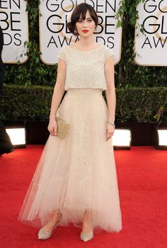 """Sugary sweet tulle skirt, chandelier earrings and a pop of red lipstick? Zooey Deschanel knows what she likes and she's sticking to it. The """"New Girl"""" actress dazzled in Oscar de la Renta."""