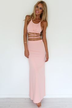 We are loving all things matching! Amazing salmon-coloured set featuring a backless halter-neck bodycon crop. Top has extra long next tie that can be crossed at back and at midriff. Paired with a high-waisted maxi skirt featuring a slightly flared bottom. Hidden zip at centre back. Unlined, not sheer. Complete the look with fine gold accessories and soft waves!