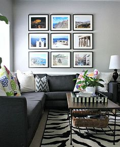 Love the drama of the large print grouping above the couch. Great colors in the photos and pillows to balance out the neutral couch, walls, and rug. #art #photos #livingroom
