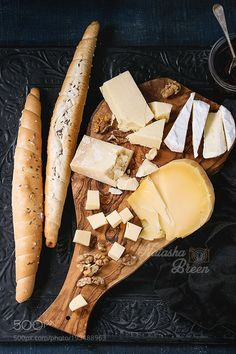 Assortment of cheese on wooden board by NatashaBreen