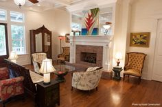 Traditional living room with a free art piece above the fireplace mantel, a brick surround fireplace, hardwood floors and classic furniture. Click on the pin to see the difference between a gas and wood-burning fireplace...