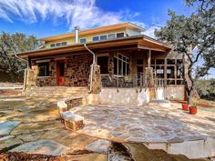 Brown stone siding and a flagstone walkway lend rustic appeal to this contemporary exterior.