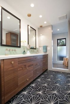 Renovated Modern Mid-Century Modern San Diego. This is a before & after house that was remodeled using lots of colorful tile. We love the green backsplash in this master bathroom featuring jack and jill sinks and wood vanity. The black tiled floor is a striking choice with an unusual pattern. Perfect for those looking for bath decor ideas
