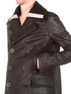 RICK OWENS FW15 SPHINX TUBE PEA COAT IN BLACK FEATURES A LAPEL COLLAR WITH PEARL GREY INSERTS ON BOTH SIDES, AN OVER THE KNEE-LENGHT, A BACK BELT, SIX BUTTONS IN FRONT,
