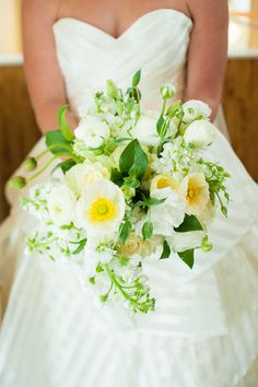 white poppies, white ranunculus, cream roses, white roses, white lisianthus and white stock are a hand tied bouquet for this florida spring bride.