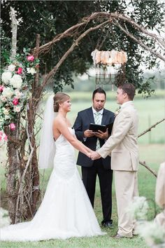 Branch wedding arch with florals for outdoor wedding ceremony.