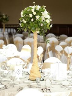 Add rustic flair to any floral centerpiece by wrapping the vase in burlap. The look works especially well when using tall, skinny vases as shown here.