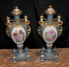 - Gorgeous pair of French Sevres style porcelain floral vases<BR> - Classic pair with bulbous amphora shape and large gilt drape serpent like handles<BR> - Floral spray panel so vivid, ready to add light to any interior<BR> - Surmountable lids and factory stamp on the underside<BR> - Classic tone of cyan blue complemented by vivid floral sprays<BR> - Come view in our Canonbury Antiques Hertfordshire showroom, just 25 minutes north of London<BR> - Available to view in the Canonbury Antiques…