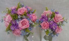 Spring tone wedding bouquets include blue hydrangea, hot escimo roses, solidago, light blue delphinium and lavender stock.  www.cobblestonedesigncompany.com