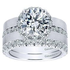 18K White Gold Wide Brushed Channel Set Diamond Engagement Ring. This ring features 1.26cttw of round channel set diamonds set in the middle of a 7mm wide band with brushed finish. Features a round di