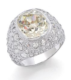 A Diamond and Platinum Ring  The broad bombé band centering a bezel-set old mine-cut diamond weighing approximately 5.70 carats, to the textured platinum ground pavé-set with small old mine-cut diamonds, tapering to a polished shank, mounted in platinum