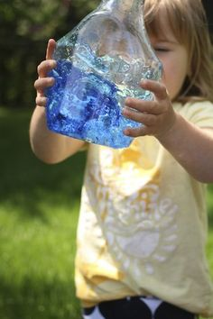 child shaking bottle of water and food colouring