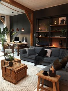 A industrial living room with a wall-mounted shelving unit, grey upholstery, wooden chests and a stool and workspace in the corner. room decor industrial Masculine Industrial Living Room With A Wall-Mounted Shelving Unit Masculine Living Rooms, House Design, Home Living Room, Industrial Livingroom, Home Decor, House Interior, Home Interior Design, Interior Design, Living Decor