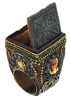 A 19th century 'Papal' ring. The large ring with square bezel mounted with a hinged iron panel revealing a velvet lined compartment, the panel engraved with the arms of the Piccolomini family, the broad tapering shoulders and sides decorated with an oval coral corallium rubrum cameo depicting a classical female head within a cut steal border and applied ribbon and V shaped motif with beaded detail, Italian, circa 1830.