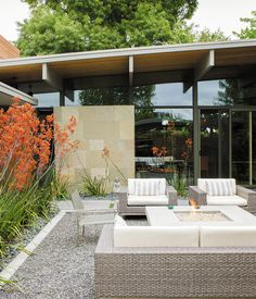 Love the stone wall with different tones patchworked  Behind the resin screen is the property's centerpiece: an entry garden that Trainor recast as an outdoor living room. Sparta stacking chairs, a deep-wicker Baia sofa, and matching Baia armchairs, all by Mamagreen, are arranged around a custom concrete fire pit. Orange kangaroo paws lean in from the