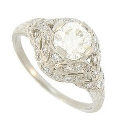 This spectacular antique style platinum engagement ring is set with a dazzling EGL certified 1.07 carat, H color, Si2 carat round cut diamond. The glittering mounting is decorated with ornate organic cutwork and frosted with an additional .33 carat total weight of fine faceted diamonds. This phenomenal wedding ring measures 11.60 mm in width. Size 7. We can re-size.