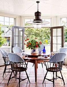 A brass station light is suspended above the breakfast area's 19th-century lazy Susan table and antique Windsor chairs | archdigest.com