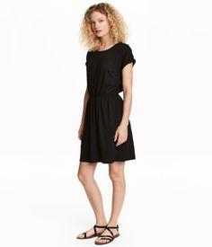 Svart. En kortärmad klänning i slubtrikå med resår i midjan. Sidfickor.