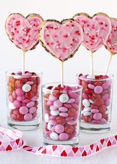 Cute presentation of a Valentine's Day dessert - heart cookies on a lollipop stick in a vase of M & M's