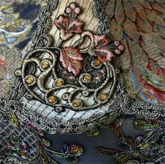 """Detail of """"Katie"""" shade featuring antique fabrics and appliqués with Baroque and Nouveau styling. Colorful 1920s lamé and art nouveau metallic appliqués with jewlels adorn the top. Shade is in tones of gold, midnight blue with accents of peachy coral. Hand-beaded fringe with European and Swarovski crystal beads."""