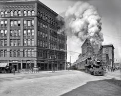 """Trains on the streets of Syracuse. c.1905-1945. """"The first street railway was built in Salina Street in 1859 and Syracuse was soon known """"far and wide"""" as the city where the trains passed through the middle of downtown. Travelers caught """"intimate glimpses"""" of the city, its people, stores and houses as the trains slowed on their way through town."""""""