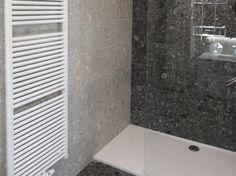 Totaalrenovatie van een badkamer in Ekeren, met inbouwkraanwerk Hansgrohe, wand- en vloertegels Mirage Norr Vitt en Norr Svart van bij RGtegel.