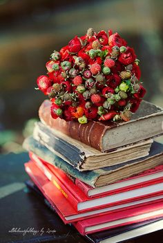 Immensely beautiful autumn bouquet stacked atop a pile of well-loved vintage books. #wedding #flowers #bouquet #vintage #books #decor #red #fall #autumn
