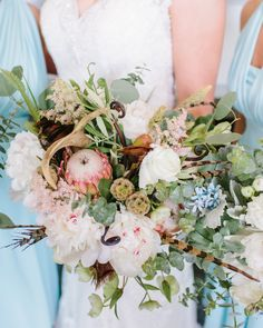 Wedding style with meaning is evident in this wildlife biologist's wedding bouquet including King Protea, scabiosa, peonies, pheasant feathers and a deer antler.