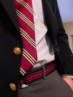Navy sport coat, white shirt with light blue stripes, red tie with yellow & navy stripes, dark grey pants