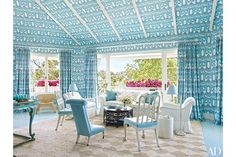 At this Bahamas home, designer Miles Redd covered the living room walls and ceiling in a China Seas fabric, with curtains to match. The sofa is by Oscar de la Renta Home for Century Furniture, the antique slipper chair is clad in a blue Global Leathers hide, the floor lamps are by Ralph Lauren Home, and the white garden seat is by Williams-Sonoma Home.