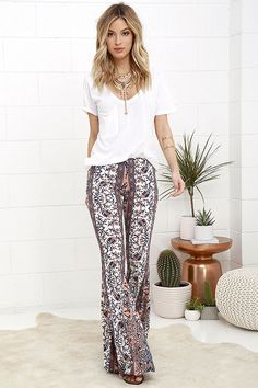 Frolic among the flowers in the Floral Festival Peach and Navy Blue Floral Print Flare Pants! Lightweight jersey knit, embellished with peach, navy blue, and ivory floral print, travels from an elastic waistband down to cute, flared pant legs.
