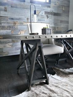 Industrial office Desk, sawhorse style, with planked feature wood wall in a rustic office.