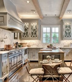 The kitchen, which set the color scheme of the home, includes the showstopper piece, the La Cornue range, and glazed cabinets with a textured finish to give a worn and distressed look. The cool plaster walls and honed statuary marble countertops, along with the polished nickel hardware set the standard for the luxury throughout the home.