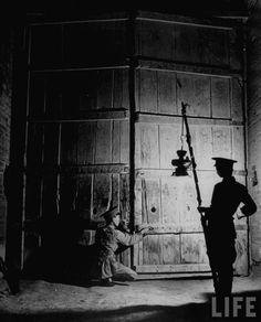 Guards closing gates for the night, Lin Tung, China by Mark Kauffman. 1947
