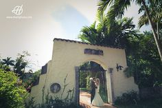 Dani and Nico wedding in Florida  photo session at Ancient Spanish Monastery in North Beach Miami  general view at the entrance with bride and groom kissing under arches photo: Doru & Claudia Halip for www.thehweddingphotography.ocm